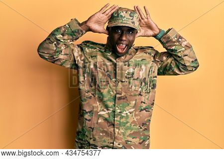 Young african american man wearing army uniform smiling cheerful playing peek a boo with hands showing face. surprised and exited