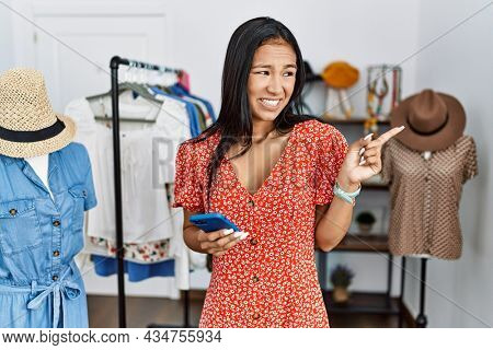 Young hispanic woman working at retail boutique using smartphone pointing aside worried and nervous with forefinger, concerned and surprised expression
