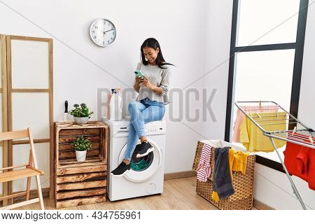 Young latin woman using smartphone waiting for washing machine at laundry room