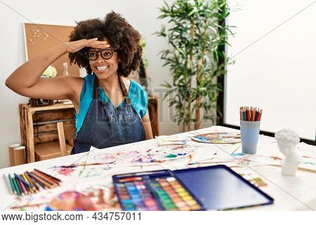 Beautiful african american woman with afro hair painting at art studio very happy and smiling looking far away with hand over head. searching concept.