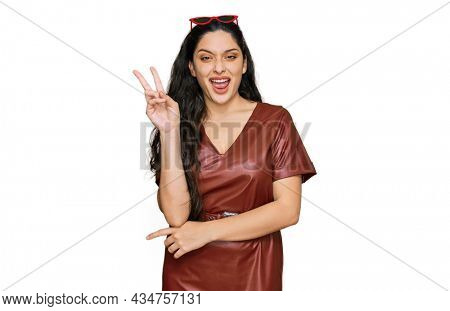 Brunette young woman wearing dress and sunglasses smiling with happy face winking at the camera doing victory sign. number two.