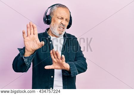 Handsome senior man with beard listening to music using headphones disgusted expression, displeased and fearful doing disgust face because aversion reaction. with hands raised