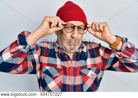 Handsome mature man holding glasses, wearing wool hat skeptic and nervous, frowning upset because of problem. negative person.