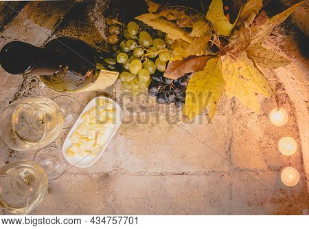 Top View Of Cheese, White Wine Glasses, Grapes And Autumn Leafs With Bottle Of Wine. Flat Lay Of Win