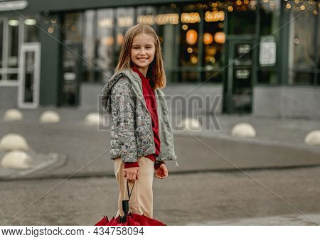 Preteen girl with umbrella in rainy evening at autumn looking at camera and smiling. Pretty kid portrait outdoors
