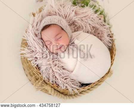 Portrait of beautiful newborn baby girl swaadled in fabric and wearing knitted hat sleeping in basket with fur during studio photoshoot. Cute infant child napping