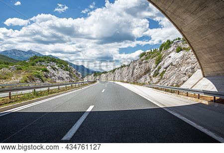 Scenic Road. The Road Is Surrounded By A Magnificent Natural Landscape And The Sunset.