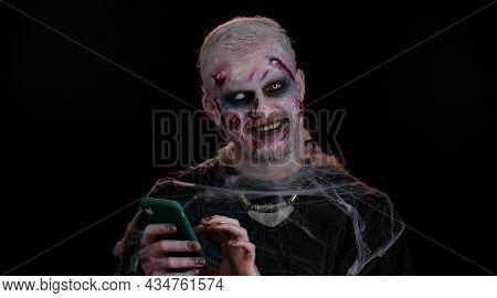 Scary Man With Halloween Zombie Bloody Wounded Makeup Using Mobile Phone Typing New Post On Web, Sms