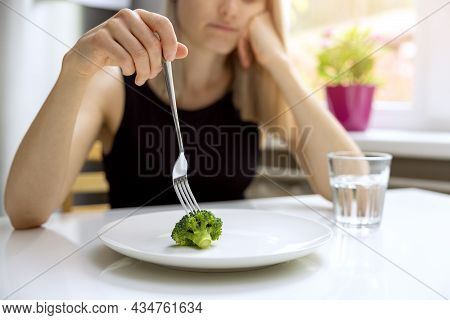 Dieting Problems, Eating Disorder - Unhappy Woman Looking At Small Broccoli Portion On The Plate