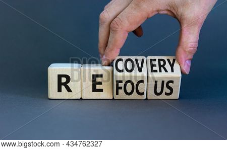 Refocus And Recovery Symbol. Businessman Turns Cubes And Changes The Word 'refocus' To 'recovery'. B