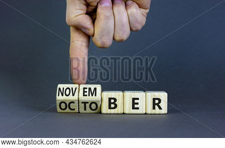 Symbol For The Change From October To November. Businessman Turns Wooden Cubes And Changes The Word