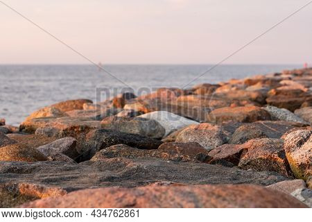 Rocks On The Beach At Sunset. Sun Is Setting Over The Rock Pier. Breakwater At Sea Coast During Pink