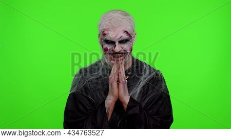 Sneaky Zombie Man Alone With Makeup With Wounds Scars With Tricky Face Gesticulating And Scheming Ev