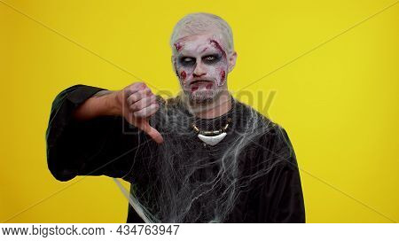 Sinister Man In Carnival Costume Of Halloween Crazy Zombie With Bloody Wounded Scars Face Showing Th