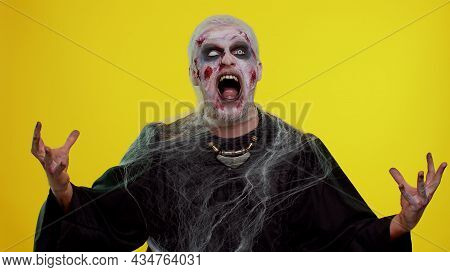 Sinister Man In Carnival Costume Of Halloween Crazy Zombie With Bloody Wounded Scars Face Screaming,
