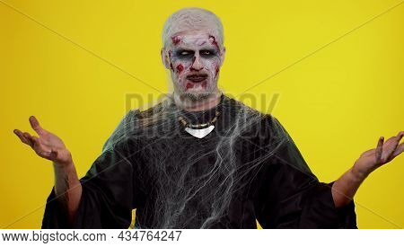 Upset Frustrated Annoyed Man Halloween Zombie Bloody Wounded Makeup Raising Hands In Indignant Expre