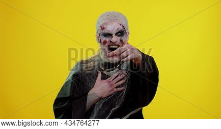 Sinister Man In Carnival Costume Of Halloween Crazy Zombie With Bloody Wounded Scars Face Pointing F