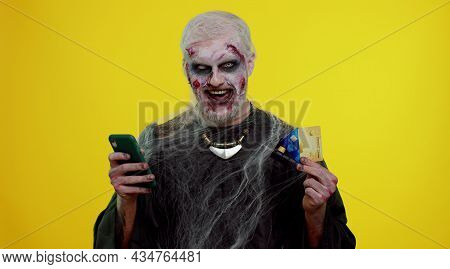 Sinister Man With Horrible Scary Halloween Zombie Make-up Using Credit Bank Cards And Mobile Phone,