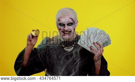 Creepy Smiling Man With Bloody Scars Face, Halloween Zombie Showing Golden Bitcoins With Money Dolla