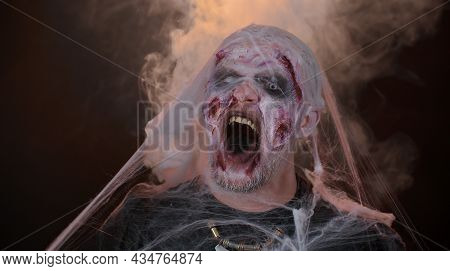 Frightening Man With Halloween Zombie Bloody Wounded Make-up Blows Smoke From Nose And Mouth, Scream