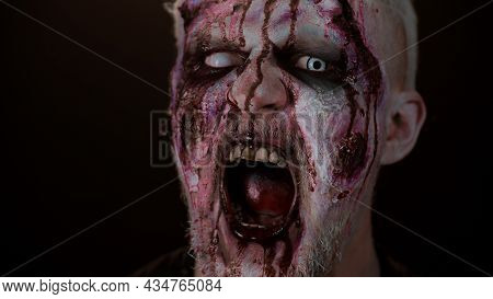 Close-up Spooky Zombie Man Face Makeup With Wounds Scars, Blood Flows And Drips On Face Trying To Sc