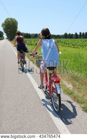 Young Girl Rides A Bicycle With Her Mom On The Road Without A Car In Summer