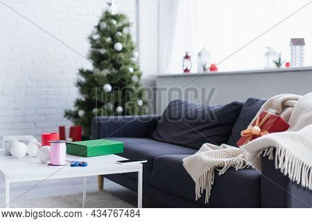 Blanket And Gift Box On Sofa Near Table With Decorative Ribbon And Scissors In Living Room With Blur