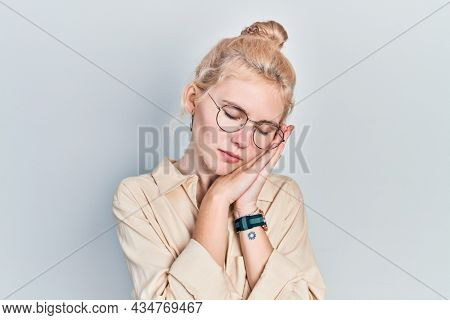Beautiful  woman with blond hair wearing casual look and glasses sleeping tired dreaming and posing with hands together while smiling with closed eyes.