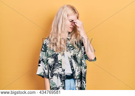 Beautiful caucasian woman with blond hair wearing tropical shirt tired rubbing nose and eyes feeling fatigue and headache. stress and frustration concept.
