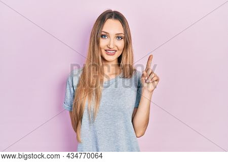 Young blonde girl wearing casual t shirt showing and pointing up with finger number one while smiling confident and happy.