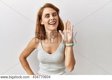 Beautiful  woman standing over isolated background waiving saying hello happy and smiling, friendly welcome gesture
