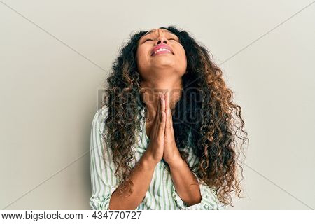 Young latin woman wearing casual clothes begging and praying with hands together with hope expression on face very emotional and worried. begging.