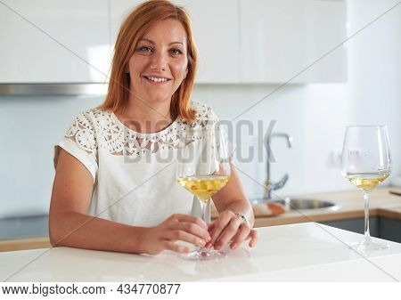 Woman relaxing with wine at home. Domestic lifestyle. Woman portrait at home. Lifestyle. Happy woman portrait people at home. Relaxed people. Young people. Portrait of woman having wine with friends at home