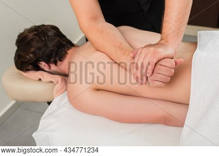 Masseur Doing Back Massage To Blurred Man In Spa Center