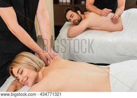 Masseur Doing Massage To Smiling Woman Near Boyfriend In Spa Center