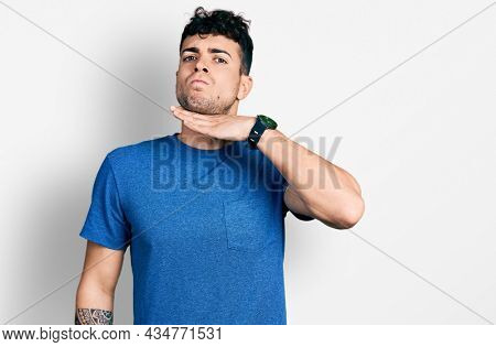 Young hispanic man wearing casual t shirt cutting throat with hand as knife, threaten aggression with furious violence