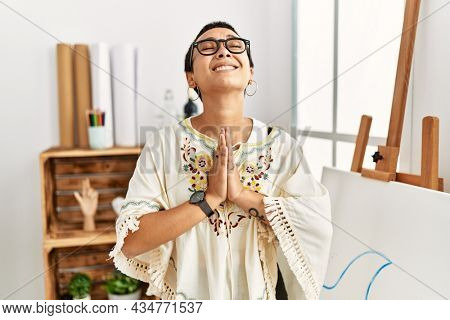 Young hispanic woman with short hair at art studio begging and praying with hands together with hope expression on face very emotional and worried. begging.