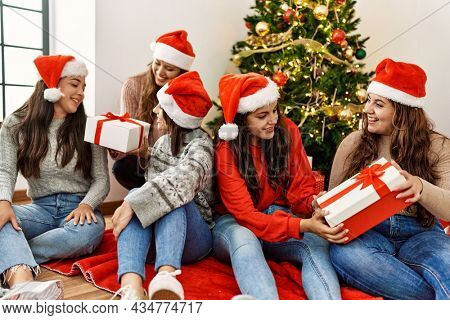 Group of young hispanic women smiling happy and holding gifts sitting on the floor by christmas tree at home.