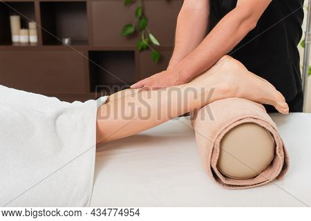 Cropped View Of Masseur Doing Massage On Leg Of Young Woman In Spa Center