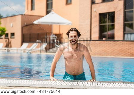 Cheerful Man Looking At Camera Near Poolside Outdoors