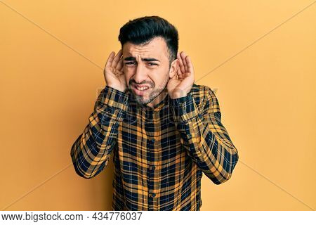 Young hispanic man wearing casual clothes trying to hear both hands on ear gesture, curious for gossip. hearing problem, deaf