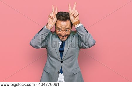 Middle age man wearing business clothes posing funny and fingers on head as bunny ears, smiling cheerful