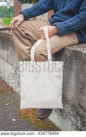 Stylish Man Holding White Blank Canvas Tote Shopping Bag