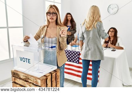 Group of young girls voting at democracy referendum pointing aside worried and nervous with forefinger, concerned and surprised expression