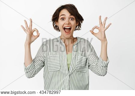 Excited Brunette Woman Look Amazed, Showing Okay Ok Sign, Approve Smth Good, Like And Agree, Praise