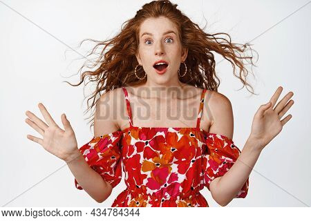 Image Of Surprised Redhead Girl Looking Amazed At Camera, Gasping In Awe, Wind Blowing At Hairstyle,