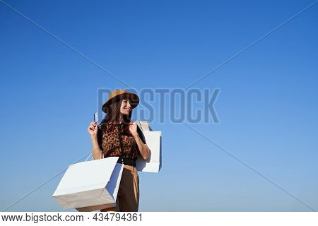 Happy Dreamy Caucasian Fashion Styled Women Holding Credit Card And White Shopping Bags On Blue Sky