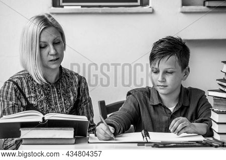 Little student during homework with the help of a tutor. Black and white photo.
