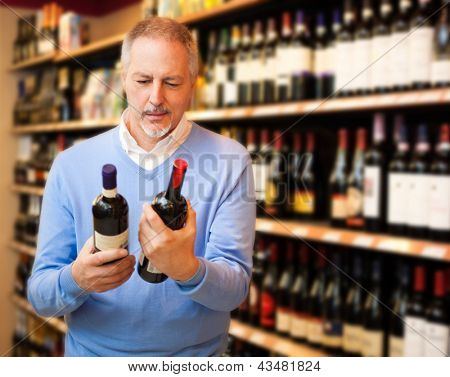 Man in a supermarket choosing the right wine
