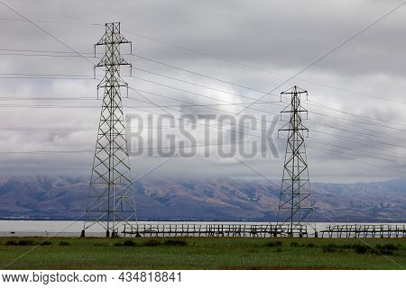 Power Lines With Scenic Marsh, Bay, Mountain Range, And Cloudy Skies. Palo Alto Baylands, Santa Clar